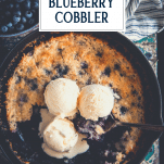 Overhead image of a skillet full of easy blueberry cobbler with vanilla ice cream on top