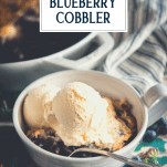 Side shot of a bowl of blueberry cobbler with vanilla ice cream and text title overlay