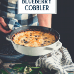 Hands holding a skillet blueberry cobbler with text title overlay