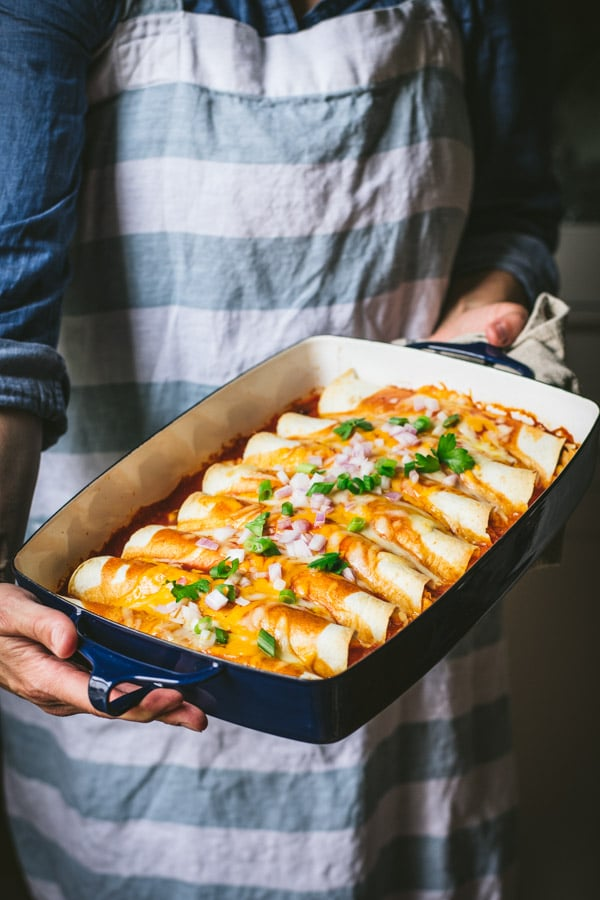 Hands holding a tray of easy chicken enchiladas