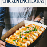 Hands holding a tray of shredded chicken enchiladas with text title box at top