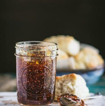 Close up side shot of a jar of homemade old fashioned fig preserves with warm biscuits