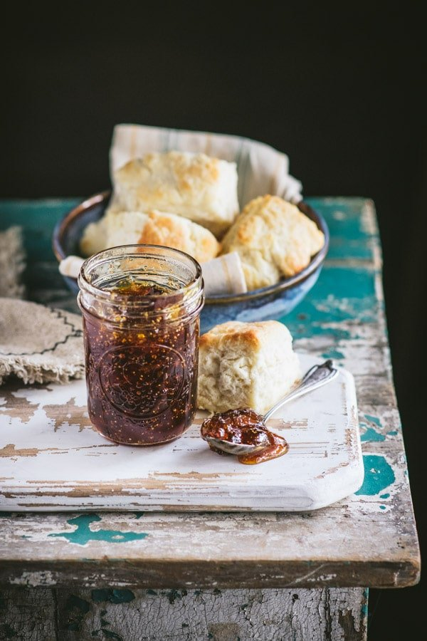 Open jar of fig jam on a wooden cutting board with biscuits