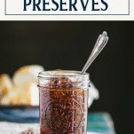 Side shot of a jar of the best fig preserves recipe with text title box at top