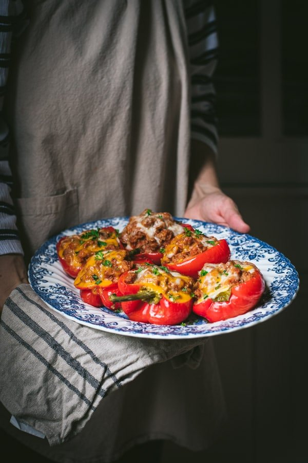 Hands holding a tray of turkey stuffed peppers.