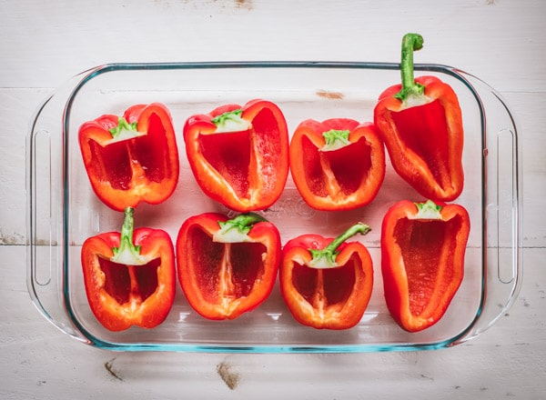 Halved red bell peppers in a glass dish.