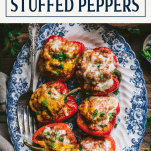Tray of ground turkey stuffed peppers on a wooden table with text title box at top
