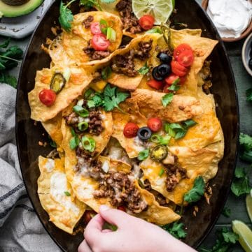 Overhead shot of a hand reaching and picking up simple homemade nachos recipe on a tray