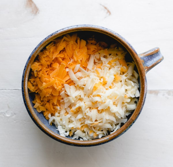 Bowl of grated cheddar and Monterey Jack cheeses