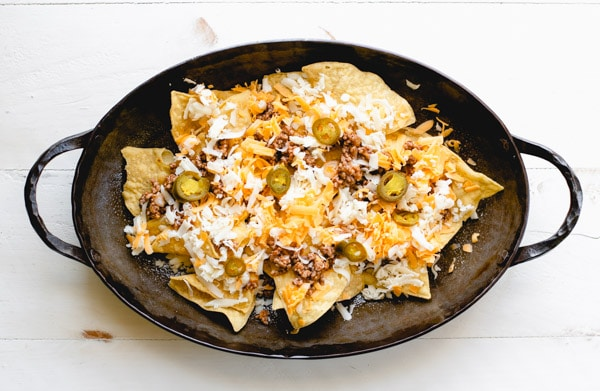 Process shot showing how to make homemade nachos with ground beef