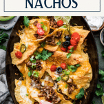 Pan of loaded homemade nachos with text title box at top