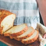 Hands holding jalapeno cheddar bread sliced on a wooden board