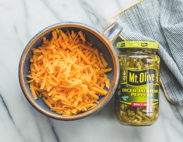 Grated cheddar cheese in a bowl and a jar of diced pickled jalapenos