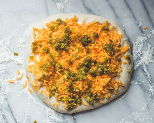 Grated cheddar and diced jalapenos on bread dough