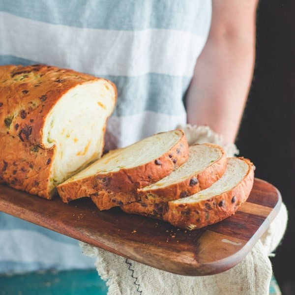 Square shot of hands holding a sliced loaf of jalapeno cheddar cheese bread on a board