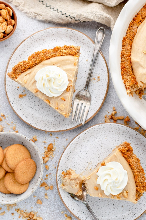 Overhead shot of two plates with peanut butter pie slices on a white surface