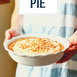 Hands holding a white plate with peanut butter pie with text title overlay