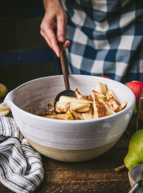Stirring together pears and warm spices in a white bowl