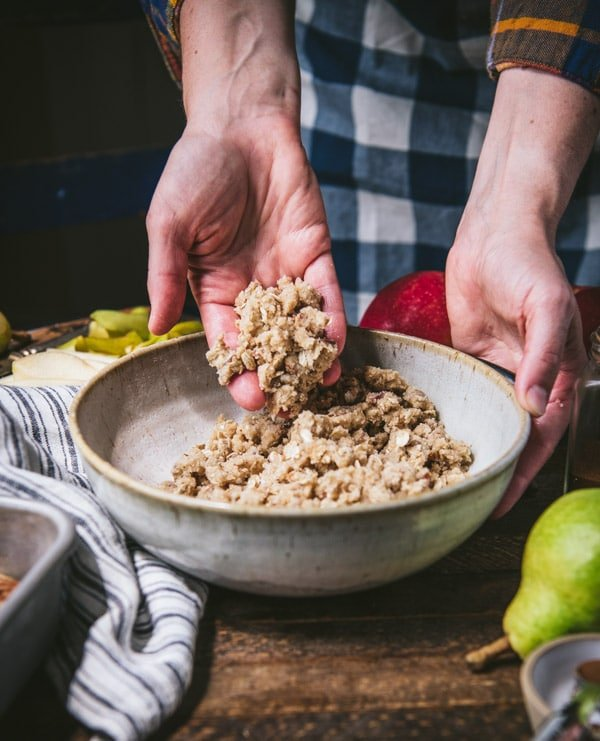 Oat streusel topping in a large white mixing bowl