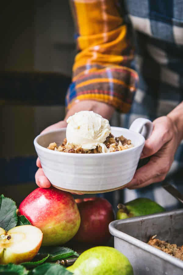 Hands holding a bowl of apple and pear crisp with oatmeal topping
