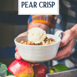 Hands holding a bowl of apple pear crisp with text title overlay
