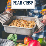 Hands holding a pan of pear crisp with text title overlay