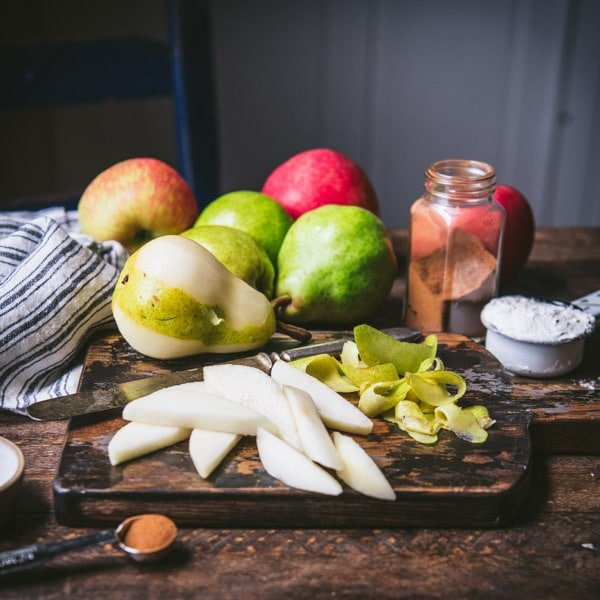 Sliced pears on a cutting board with apples in the background