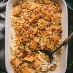 Overhead shot of an easy poppy seed chicken casserole with almonds on a wooden table