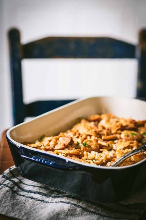 Side shot of a dish of poppy seed chicken casserole on a dinner table.