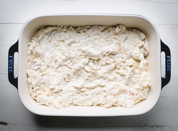 Creamy poppy seed chicken casserole filling in a dish