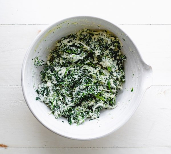 Spinach and ricotta mixture in a white mixing bowl