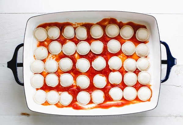 Frozen cheese ravioli in a baking dish with marinara sauce