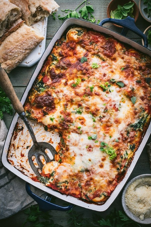 Overhead shot of a serving spoon in a pan of oven baked ravioli casserole