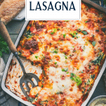 Serving spoon in a pan of baked ravioli with text title overlay