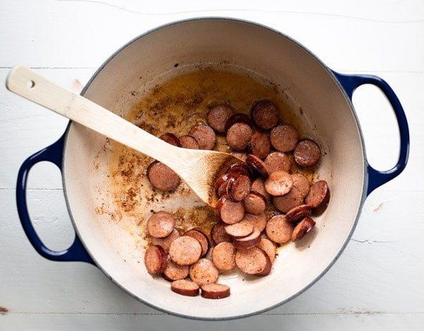 Browning andouille sausage in a pot