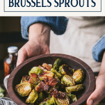 Hands holding a wooden bowl of crispy roasted brussels sprouts with text title box at top