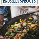 Roasting pan full of crispy roasted brussels sprouts with bacon and text title box at top