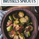 Close overhead shot of roasted brussels sprouts in a wooden bowl with text title box at top