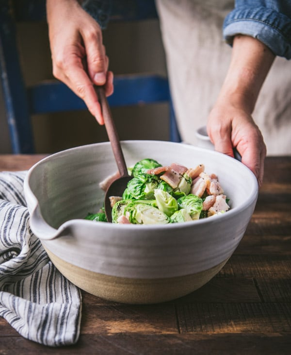 Stirring brussels sprouts and bacon in a white bowl