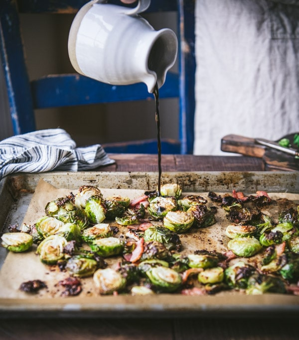 Drizzling maple syrup and balsamic vinegar over a pan of oven roasted brussels sprouts