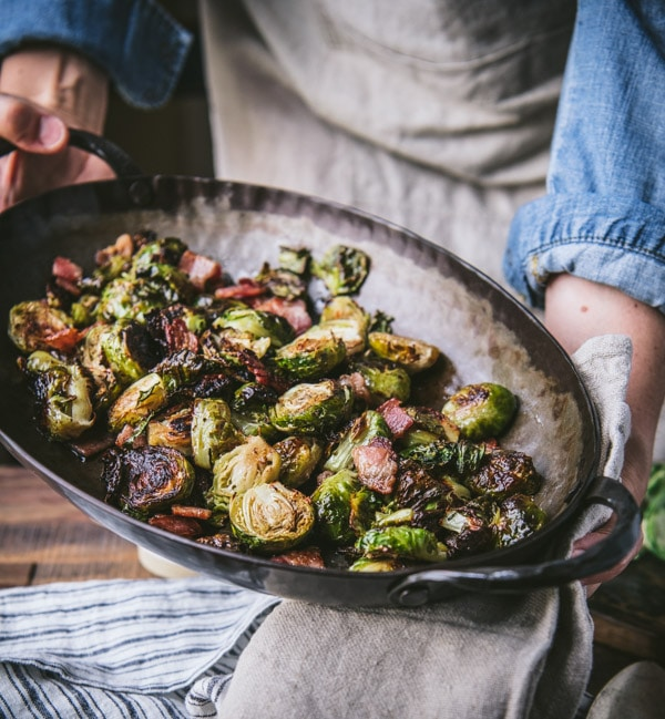 Oven roasted brussels sprouts with bacon in a cast iron pan