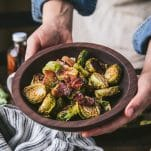 Hands holding a bowl of oven roasted brussels sprouts with balsamic and bacon