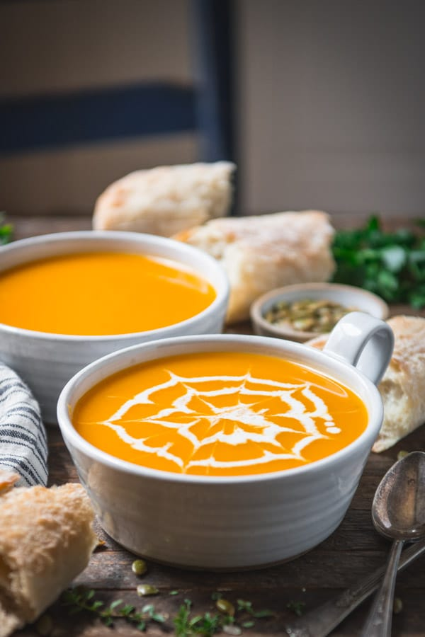 Two bowls of roasted butternut squash soup on a farmhouse table served with bread