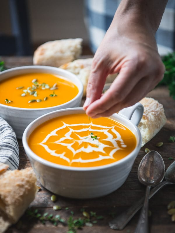 Sprinkling fresh thyme on a bowl of the best butternut squash soup recipe