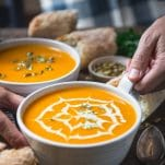 Side shot of hands holding a bowl of roasted butternut squash soup