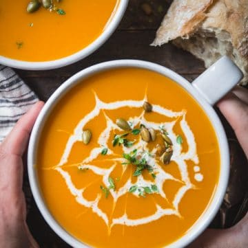 Overhead shot of hands holding a white bowl full of simple butternut squash soup
