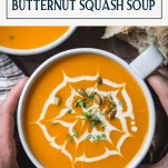Overhead image of hands holding a bowl of roasted butternut squash soup with text title box at top