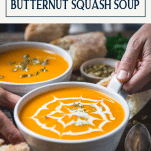 Hands holding a bowl of easy butternut squash soup with text title box at top