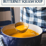 Ladle in a pot of roasted butternut squash soup with text title box at top
