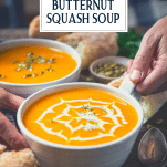 Hands holding a bowl of roasted butternut squash soup with text title overlay